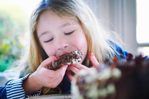 menina comendo bolo de chocolate